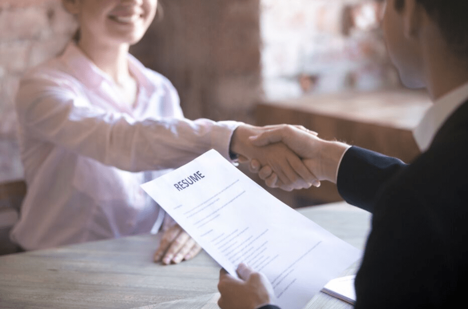 A man and woman shaking hands during a job interview.