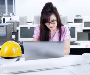 An office worker sitting at her desk on her computer next to her hard hat. She is following workplace safety guidelines.